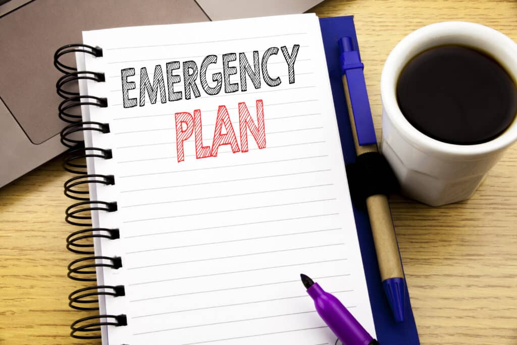 notebook with words emergency plan for disaster recovery planning